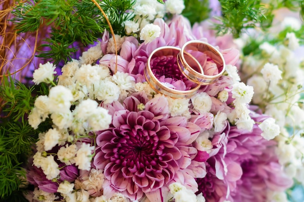 Dois anéis de casamento de ouro estão nas flores de um lindo buquê