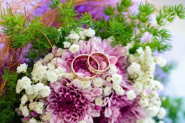 Dois anéis de casamento de ouro mentem sobre as flores de um buquê close-up