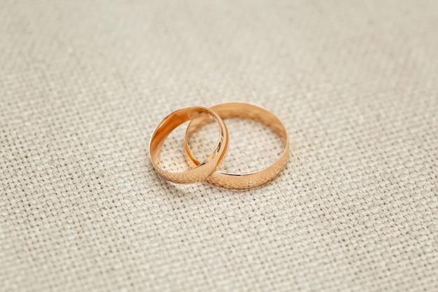 Dois anéis de casamento de ouro na superfície bege, close-up