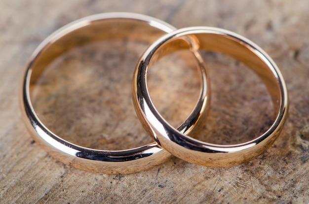 Dois anéis de casamento de ouro sobre fundo de madeira