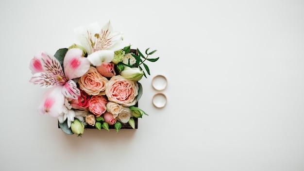 Dois anéis de casamento dourados dispostos perto da composição de flores bonitas e fofas em uma caixinha
