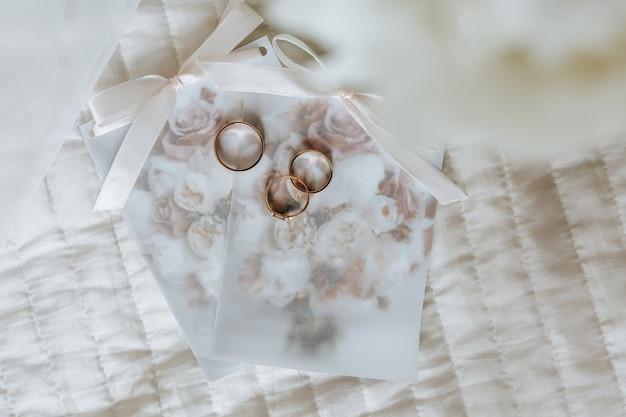 Dois anéis de casamento e um anel de noivado repousam sobre um convite com superfície de flores
