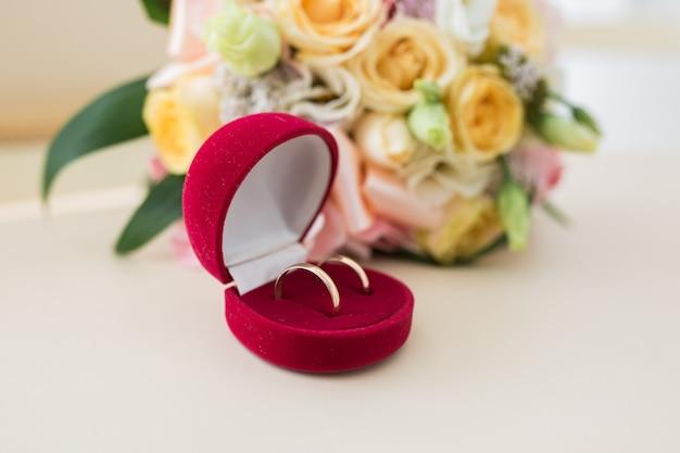 Dois anéis de casamento em caixa vermelha e flores de primavera. conceito de casamento.