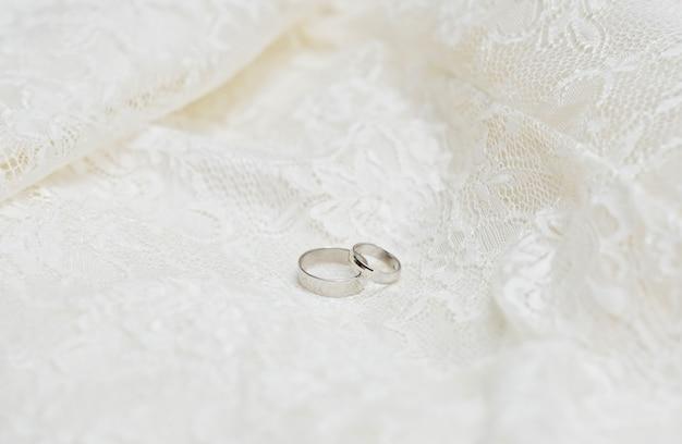 Dois anéis de casamento em um fundo de renda branca