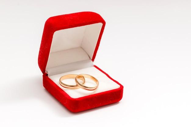 Dois anéis de casamento em uma bela caixa vermelha isolada no fundo branco