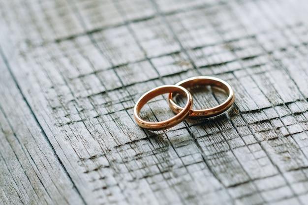 Dois anéis de casamento em uma textura de madeira
