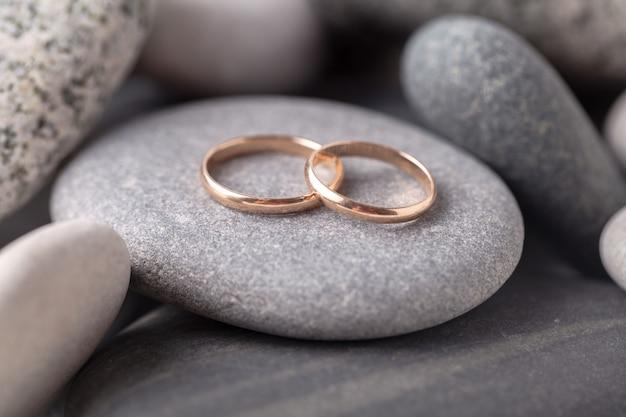 Dois anéis de casamento encontram-se na rocha do mar