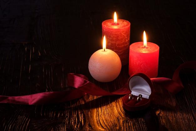 Dois anéis de casamento na caixa de presente vermelha com três velas de chama de cera com fita na luz romântica escura, amor namoro, dia dos namorados, foco seletivo