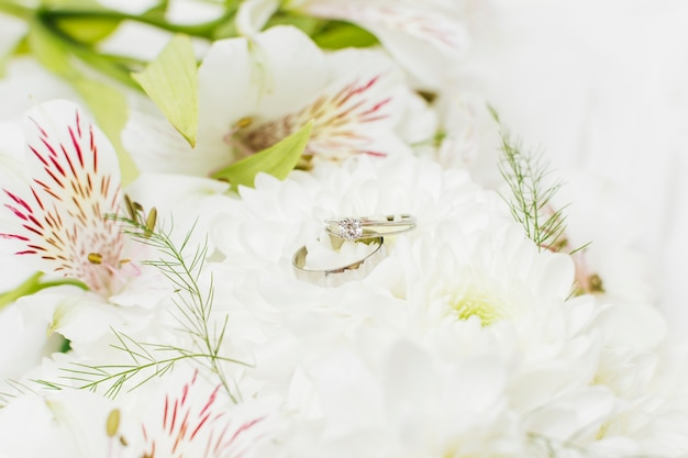 Dois anéis de casamento no crisântemo bonito e flores de lírio peruano