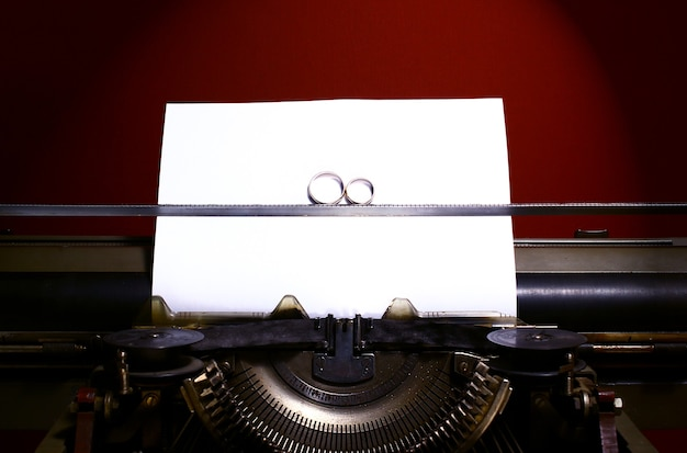 Dois anéis de casamento no infinito assinam em uma máquina de escrever. conceito de voto de casamento.