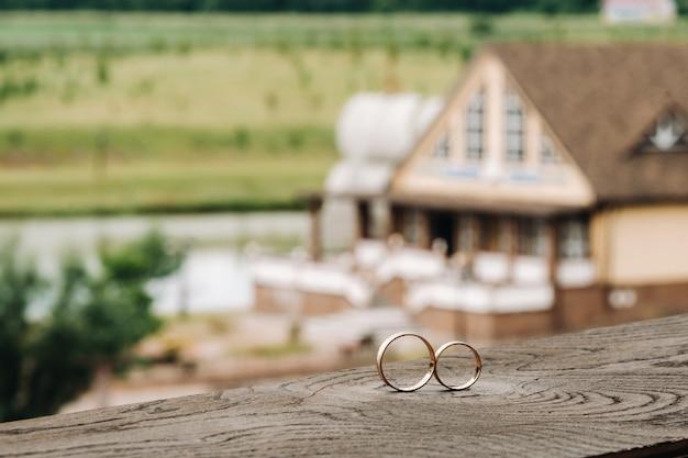 Dois anéis de noivado em uma base de madeira para um anel de ouro de um casal de noivos