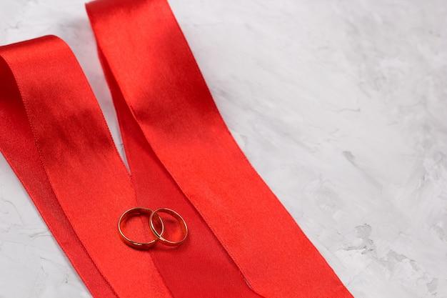 Dois anéis de ouro e decoração de casamento de fita de cetim vermelho ou conceito de fundo de convite de casamento