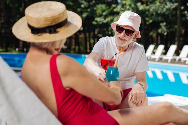 Dois aposentados com estilo moderno comemorando aniversário de casamento perto da piscina