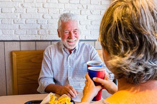 Dois aposentados comendo juntos em fast food ou restaurante - idosos se encontrando no primeiro encontro tilintando com a xícara - homem sorrindo olhando para a mulher madura