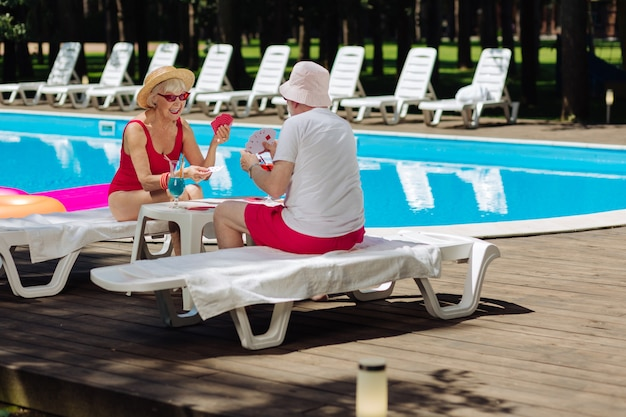 Dois aposentados felizes e radiantes jogando cartas juntos enquanto estão sentados na espreguiçadeira perto da piscina