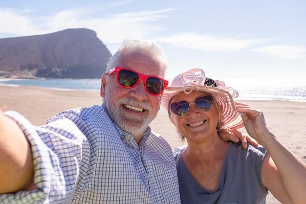 Dois aposentados juntos tirando uma selfie na praia sorrindo e olhando para a câmera com o mar