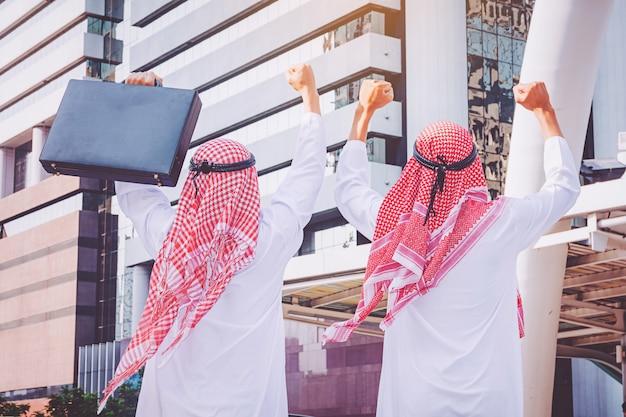 Dois, árabes, homens negócios, ficar, levantando, ambos, mãos cima, em, cidade