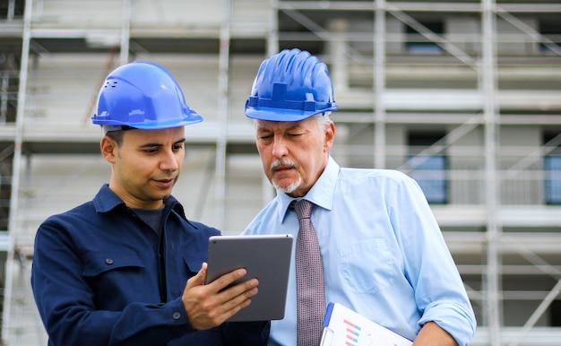 Dois arquitetos desenvolvedores revisando os planos de construção no canteiro de obras usando um tablet