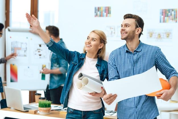Dois arquitetos designers posando com papéis.