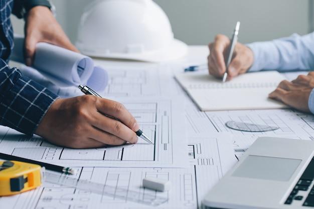 Dois arquitetos discutindo um projeto e trabalhando em uma planta no canteiro de obras do escritório