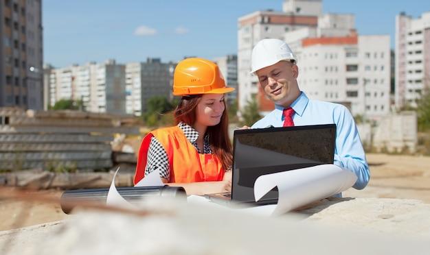 Dois arquitetos em frente ao local de construção