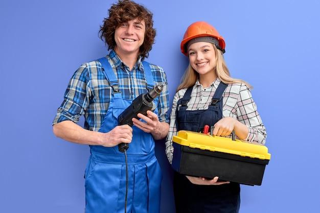 Dois arquitetos em macacões uniformes estão de pé com ferramentas e instrumentos posando isolados no azul