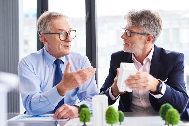 Dois arquitetos maduros discutindo estratégia de negócios