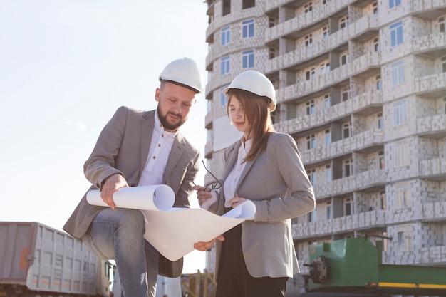 Dois, arquitetos, segurando, blueprint, e, discutir, projeto, enquanto, trabalhando, junto