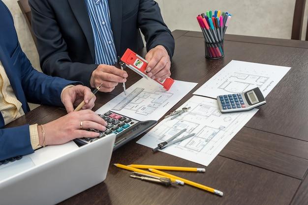 Dois arquitetos sócios que trabalham em houme desenham a construção com laptop e ferramentas no escritório. projeto do arquiteto