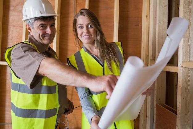 Dois arquitetos sorridentes com planos