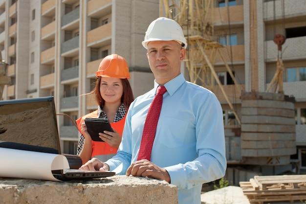 Dois arquitetos trabalham em frente ao local de construção