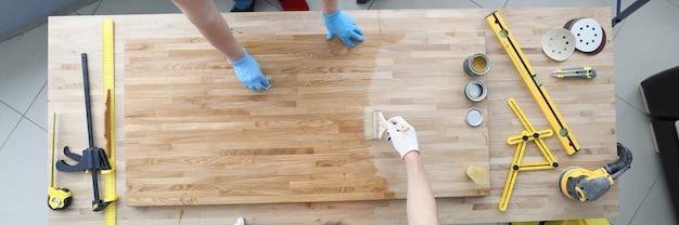 Dois artesãos cobrem a mesa de madeira com verniz protetor