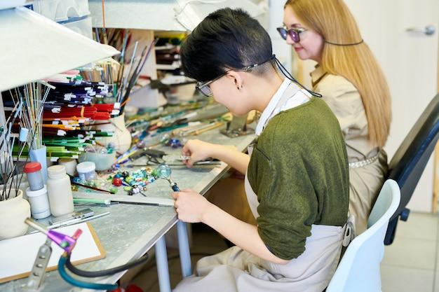 Dois artistas femininos trabalhando no estúdio de vidro
