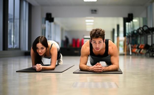Dois atletas fazendo flexões em uma academia