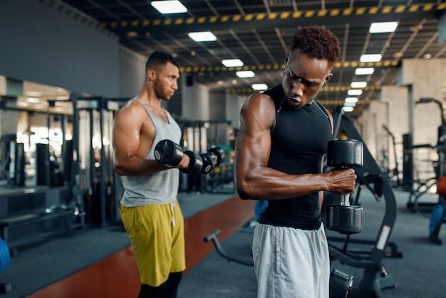 Dois atletas musculosos fazendo exercícios com halteres no treinamento no ginásio.