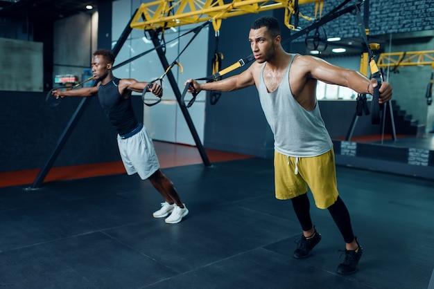 Dois atletas musculosos no sportswear no alongamento da máquina de exercícios no treinamento no ginásio.