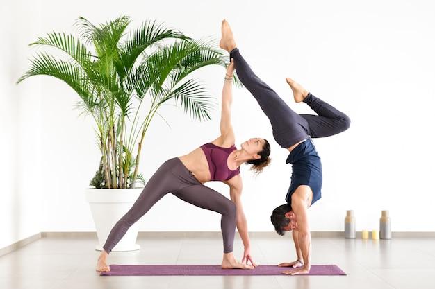 Dois atletas realizando duo acroyoga poses