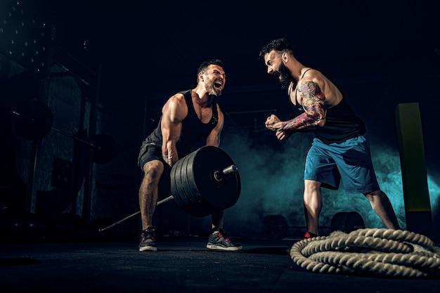 Dois atletas tatuados barbudos musculares treinando na academia