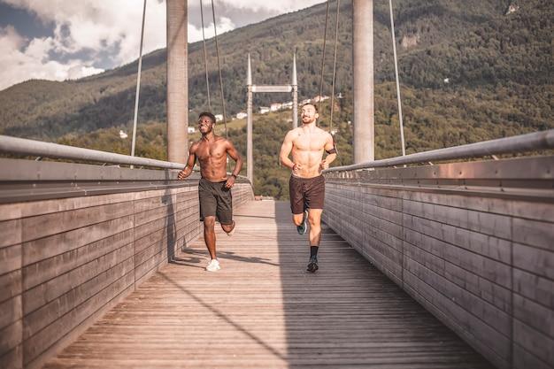 Dois atletas treinam correndo no deck de madeira.