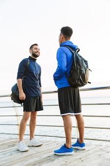 Dois atractivos jovens desportistas saudáveis ao ar livre na praia, a conversar