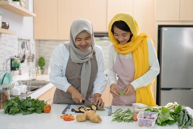 Dois atraente jovem muçulmana preparando o jantar iftar juntos.