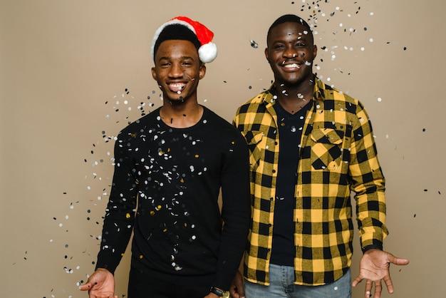 Dois atraentes gays negros elegantes estão celebrando a festa de ano novo, casal homossexual jogando confete, parabenizando um ao outro no fundo bege.