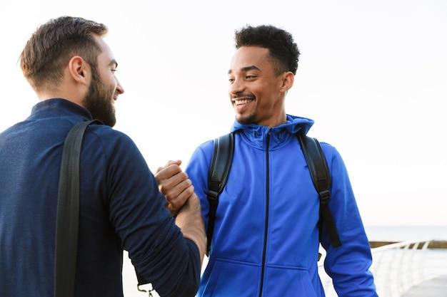 Dois atraentes jovens esportistas saudáveis e sorridentes ao ar livre na praia, apertando as mãos