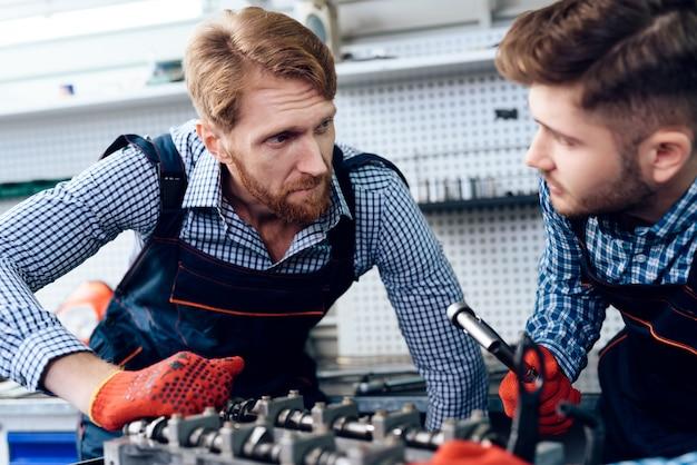 Dois auto mecânicos estão verificando o detalhe na garagem.