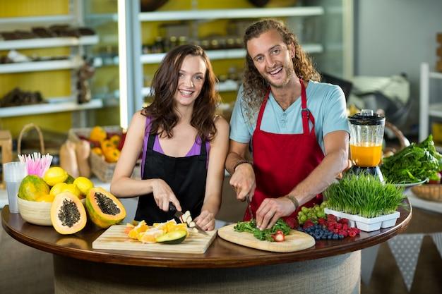Dois balconistas cortando legumes e frutas no balcão