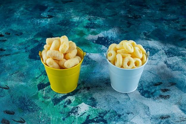 Dois baldes de palito de milho e anel de milho, na mesa de mármore.