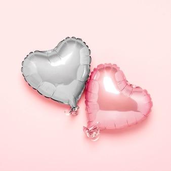 Dois balões de ar rosa em forma de coração em uma superfície rosa. conceito dia dos namorados