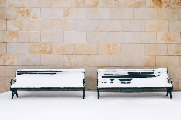 Dois bancos cobertos de neve contra uma parede de tijolos no inverno