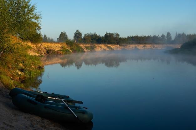 Dois barcos de borracha com apetrechos de pesca no início da manhã durante o nevoeiro, estacionados nas margens do rio.