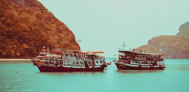 Dois barcos de viagem param no mar com pequena ilha